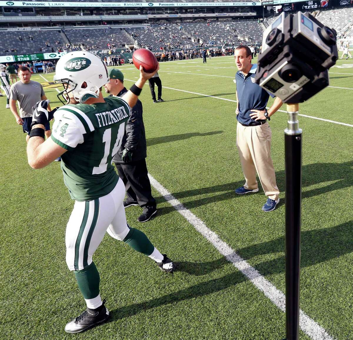 New York Jets quarterback Ryan Fitzpatrick warms up before Sunday's game against the Tennessee Titans as cameras film him.