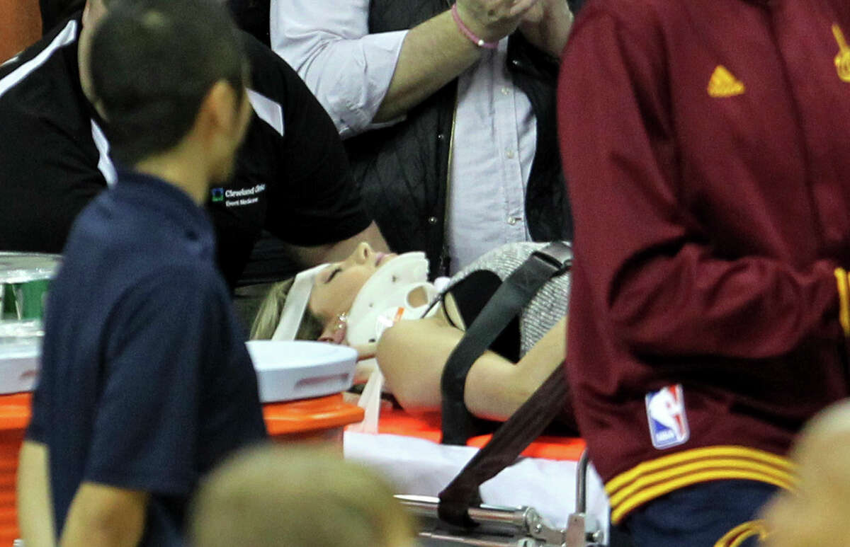 Ellie Day, wife of PGA Tour player Jason Day, is carried off the floor in a stretcher after the Cavaliers' LeBron James collided with her out of bounds during Thursday's game against the Thunder in Cleveland.