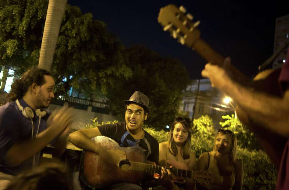 Youths sing and play music as they hang out in a park in Havana, Cuba, late Friday, Dec. 19, 2014. For a generation that grew up believing the best way to pursue their dreams was to leave the island, the announcement this week that Cuba will open relations with the U.S. is prompting many to reevaluate their futures. Photo: AP Photo/Ramon Espinosa  / AP