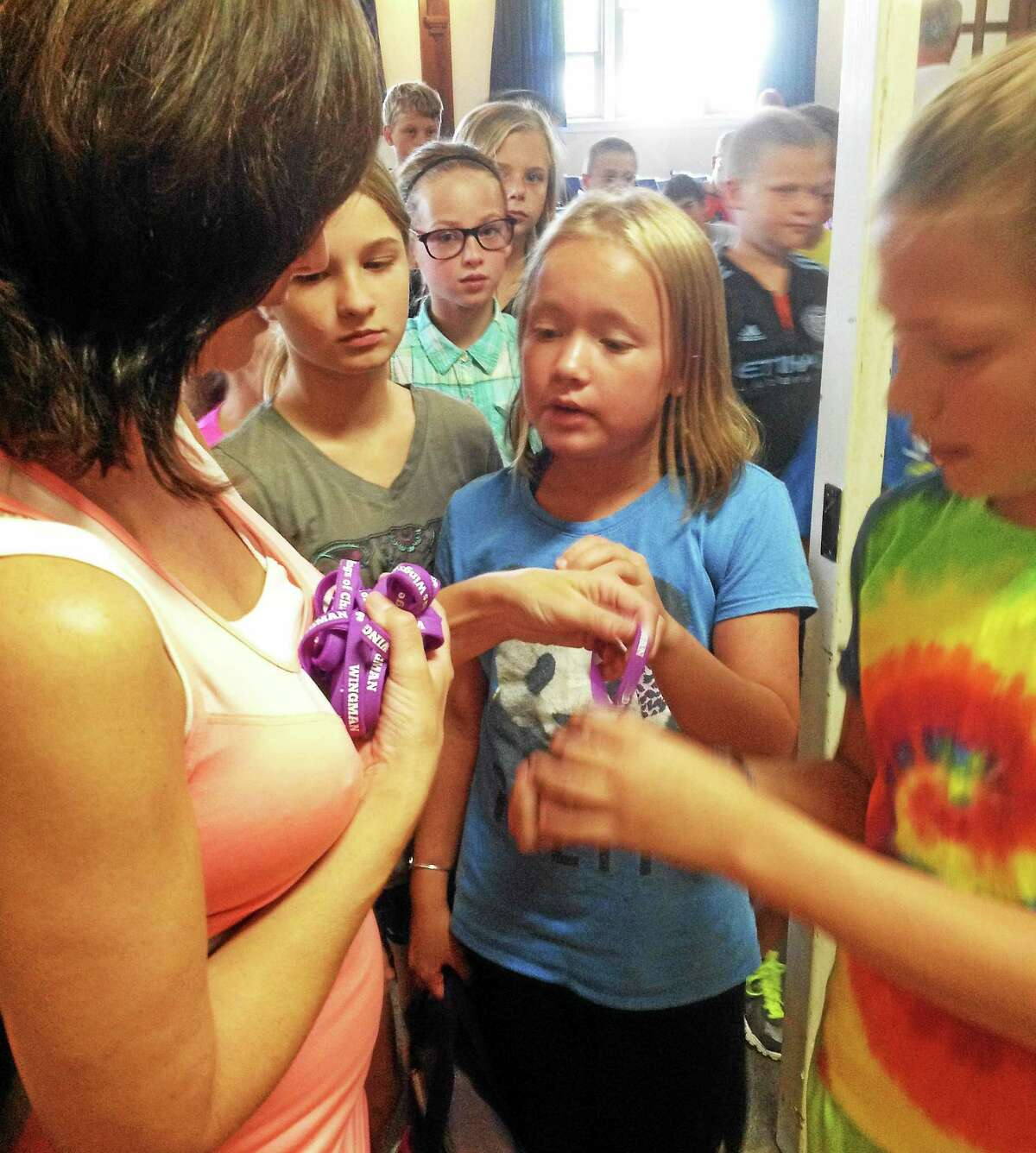 Portland Brownstone Intermediate School students gather around for a purple Dylan's Wings of Change bracelet Friday.