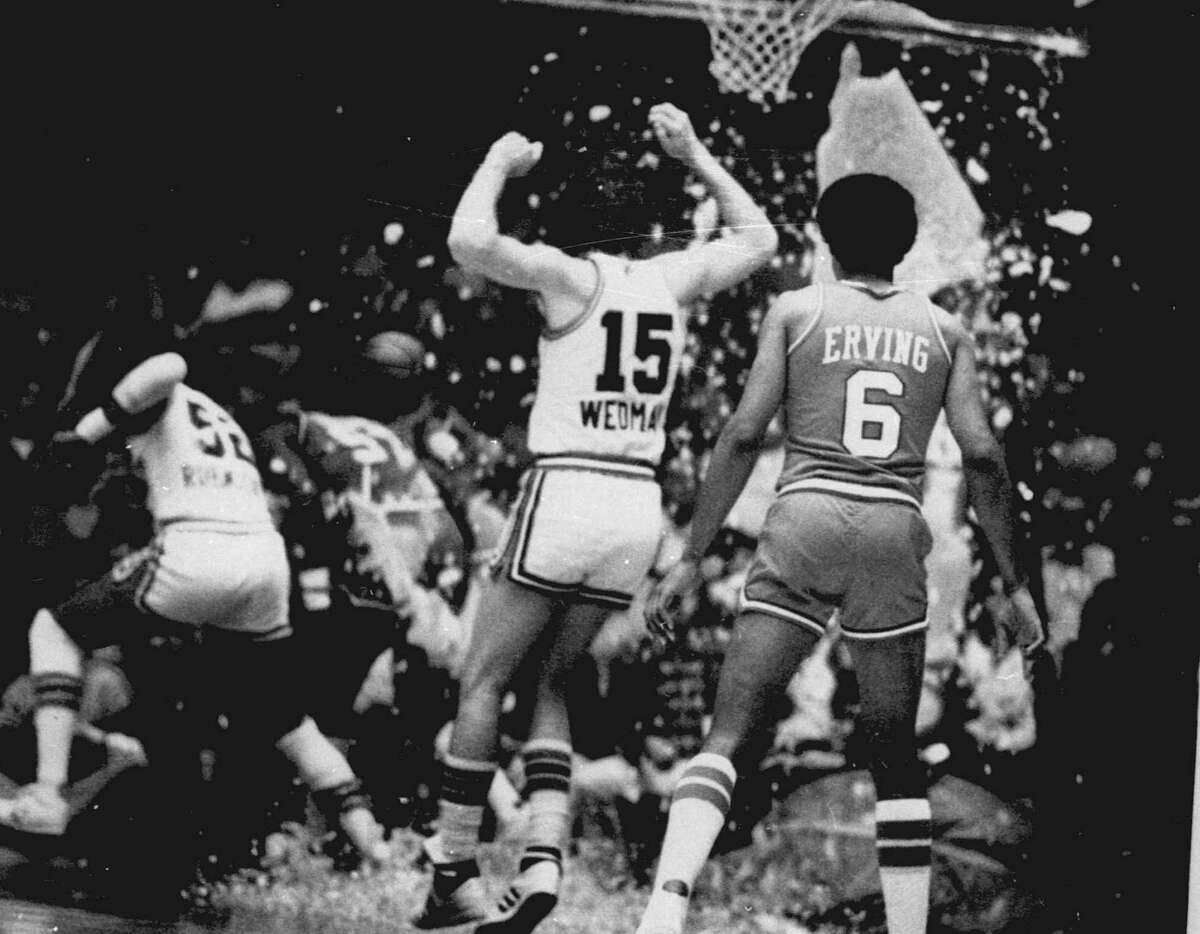 This November 1979 file photo shows players ducking for cover after the Philadelphia 76ers' Darryl Dawkins shattered the backboard during a game in Kansas City, Mo.