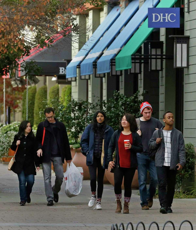 Shoppers walk through an outdoor mall Thursday, Dec. 17, 2015, in Alameda, Calif. (AP Photo/Ben Margot)