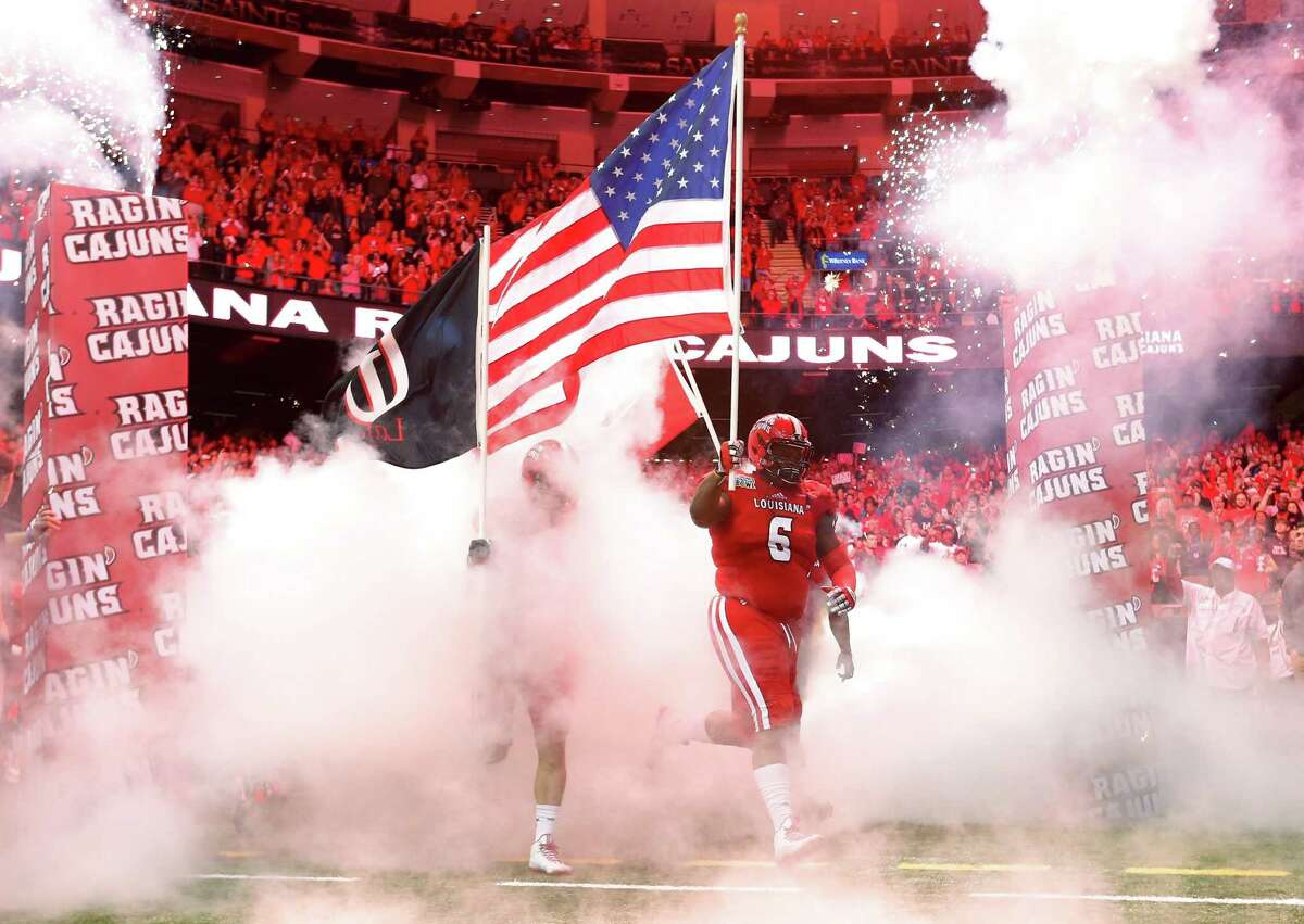 Louisiana-Lafayette defensive lineman Justin Hamilton carries an American flag out to the field before the New Orleans Bowl against Nevada on Saturday.