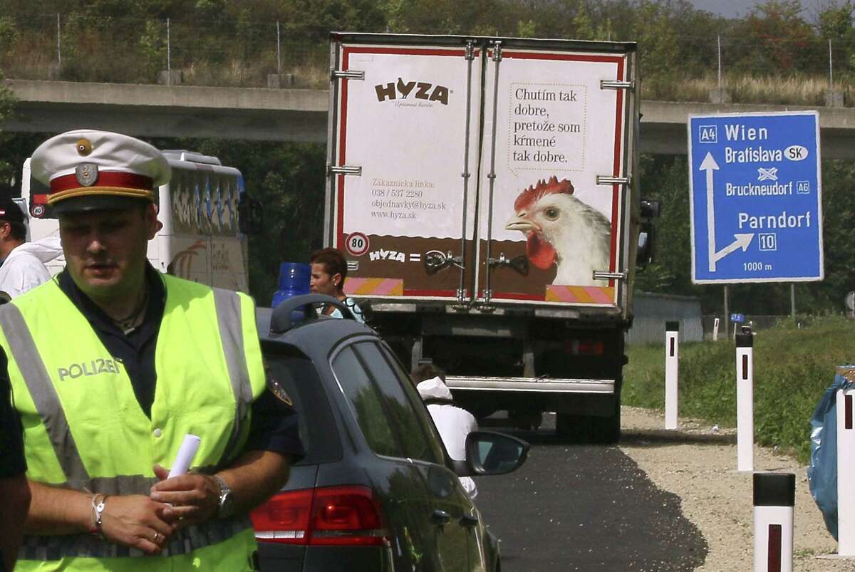 Police stand in fron of a truck parked on the shoulder of the highway A4 near Parndorf south of Vienna, Austria, Thursday, Aug 27, 2015. At least 20 migrants were found dead in the truck parked on the Austrian highway leading from the Hungarian border, police said.