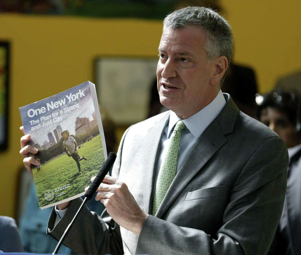 New York City Mayor Bill de Blasio holds up a copy of the