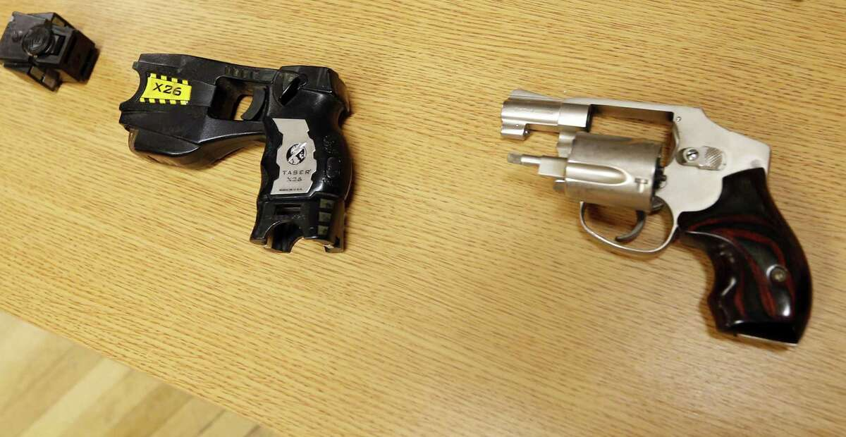 In this April 10, 2015 photo, a Taser and handgun are displayed at a news conference in Tulsa similar to the weapons in possession of Tulsa County reserve deputy Robert Bates who killed an unarmed suspect in Tulsa.