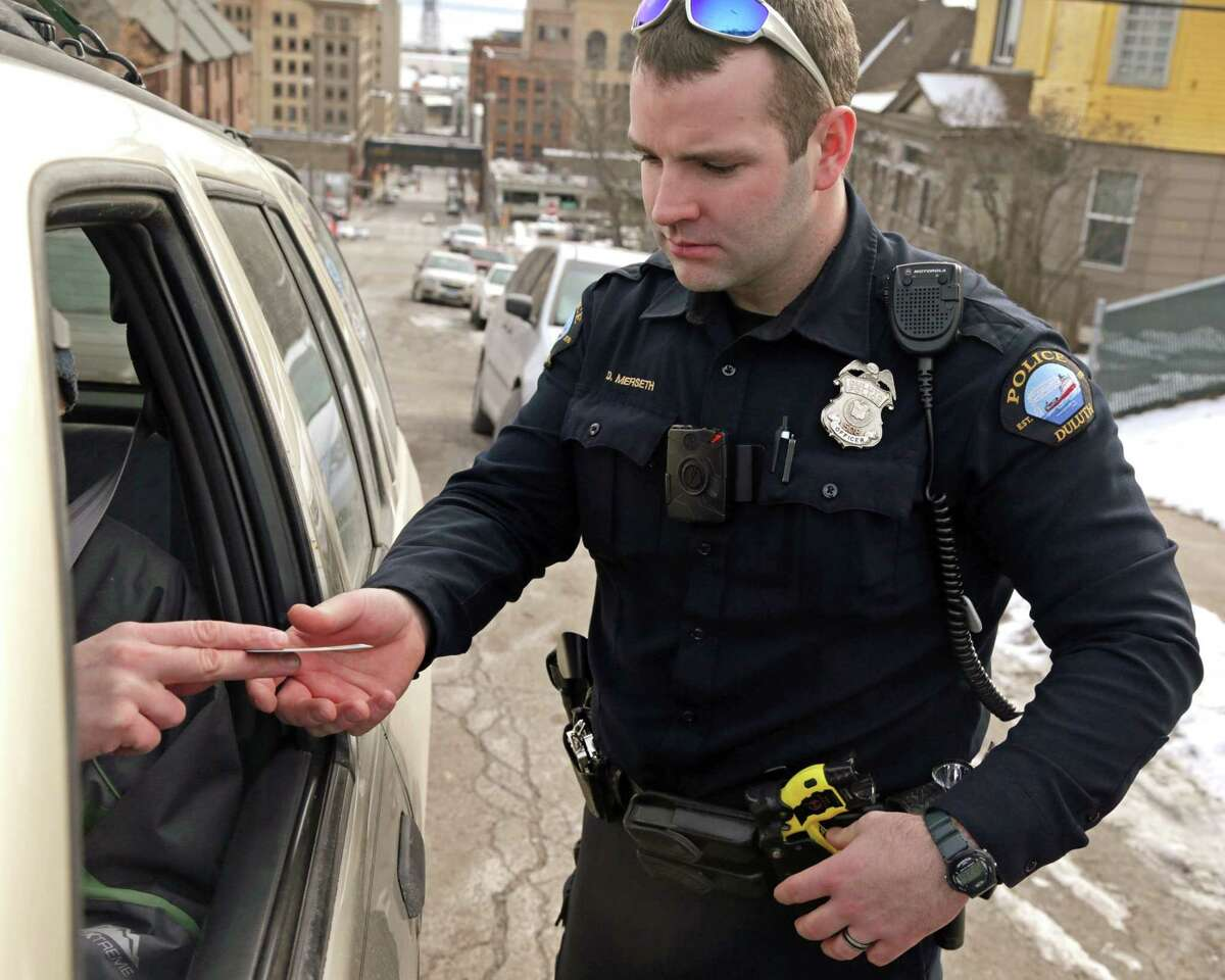 In this Feb. 2, 2015 photo, Duluth Police Officer Dan Merseth wears a taser on his left side and a handgun on his right side during a traffic stop in Duluth, Minn.