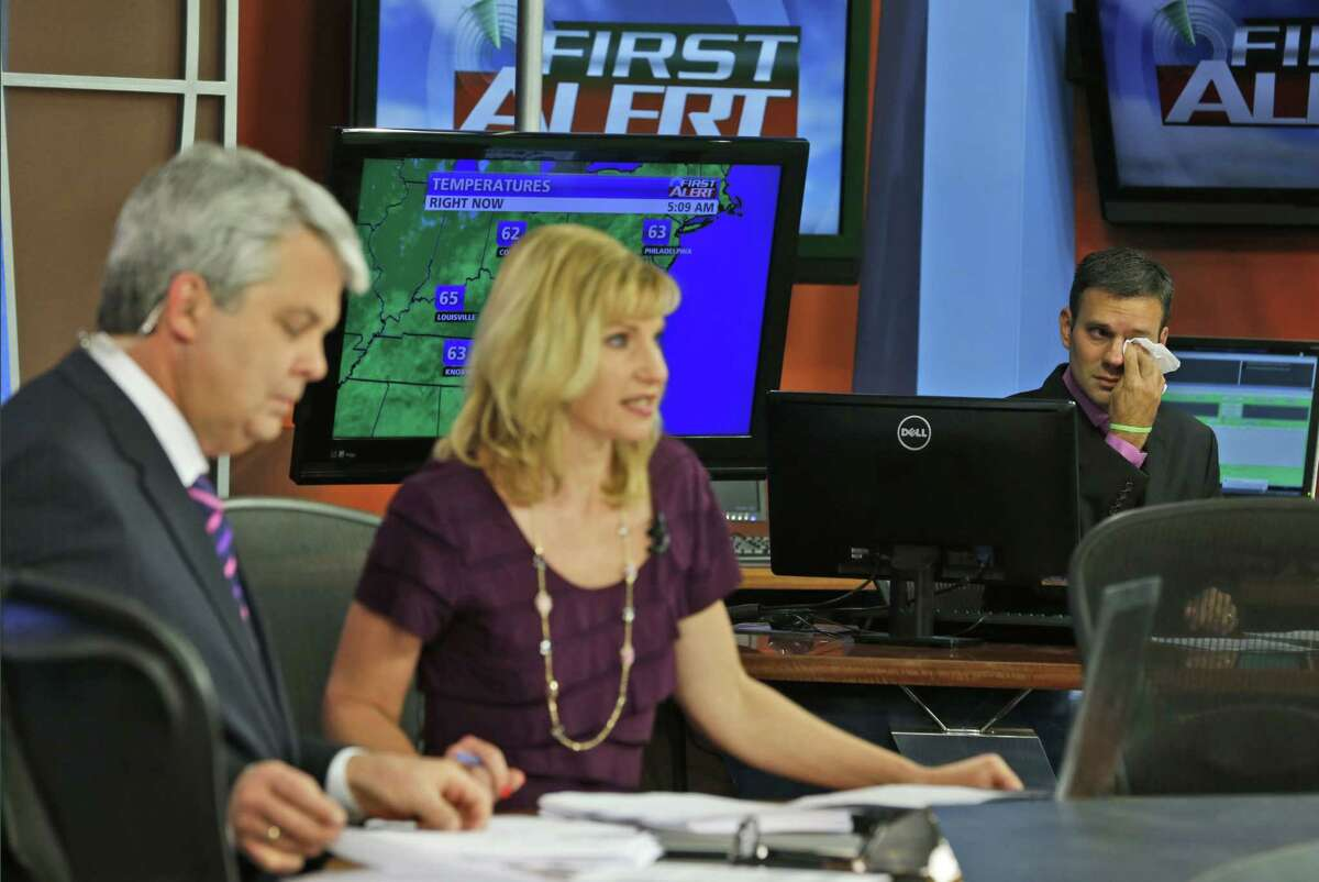 WDBJ-TV7 meteorologist Leo Hirsbrunner, right, wipes his eyes during the early morning newscast as anchors Kimberly McBroom, center, and guest anchor Steve Grant deliver the news at the station in Roanoke, Va. on Thursday, Aug. 27, 2015. Reporter Alison Parker and cameraman Adam Ward were killed during a live broadcast Wednesday, while on assignment in Moneta.