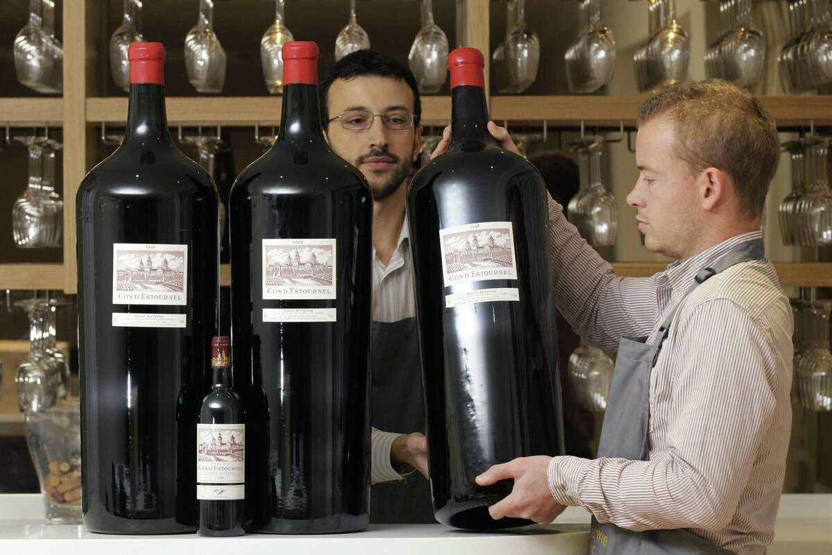 """This is a Thursday, Nov. 17, 2011, file photo of Antique Wine Company's employees poses with three Melchiors and a standard size bottle of Cos D'Estournel wine at the wine merchant in London, Thursday, Nov. 17, 2011. A Melchior holds 18 litres, 24 bottles or 102 glasses of wine. The free online dictionary of current usage, created by the publishers of the venerable Oxford English Dictionary, issued its quarterly update Thursday Aug. 27, 2015, of new words that have gained widespread currency in the English language. From the list comes, """"wine o'clock"""" the appropriate time of day to start drinking wine."""