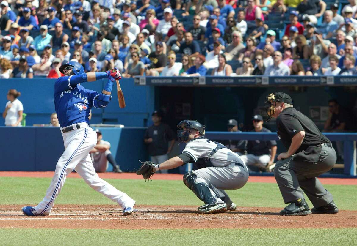 The Blue Jays' Jose Bautista, left, hits a two run home run in the first inning Saturday.