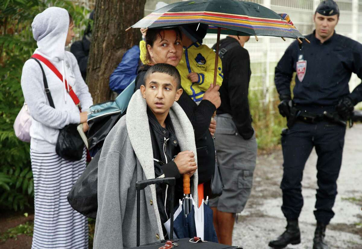 A Roma, also known as Gypsy, argues with French police officer as police dismantle sprawling Roma camp in La Courneuve, on Paris outskirts, France, Thursday, Aug. 27, 2015. Police are clearing out one of Franceís biggest and oldest Roma camps, a sprawling network of makeshift shelters that has housed about 200-300 people for at least three years, mostly from eastern Europe.
