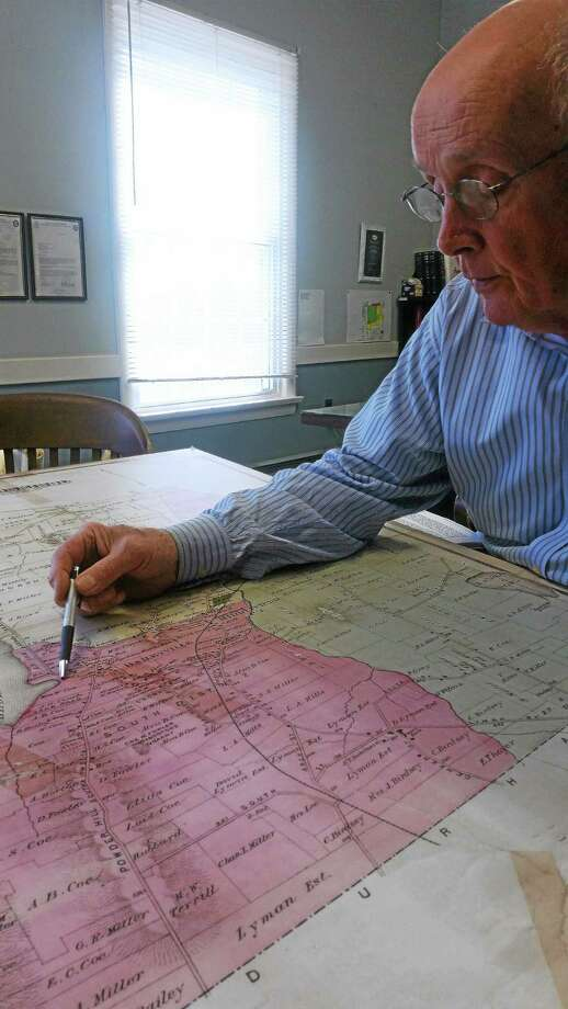 First Selectman Jon Brayshaw reviews a map of the town at his office on Wednesday. Photo: Journal Register Co.