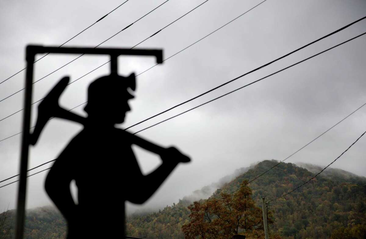 Fog hovers over a mountaintop as a cut out of a coal miner stands at a memorial to local miners killed on the job in Cumberland, Ky.