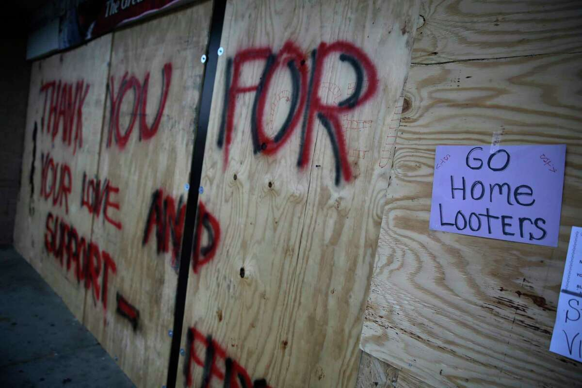 FILE - in this Aug. 18, 2014 file photo, a message is written on a boarded up liquor store in Ferguson, Mo. Businesses that were victimized by looting are slowly coming back as signs of healing are beginning to dot the area. (AP Photo/Jeff Roberson, File)