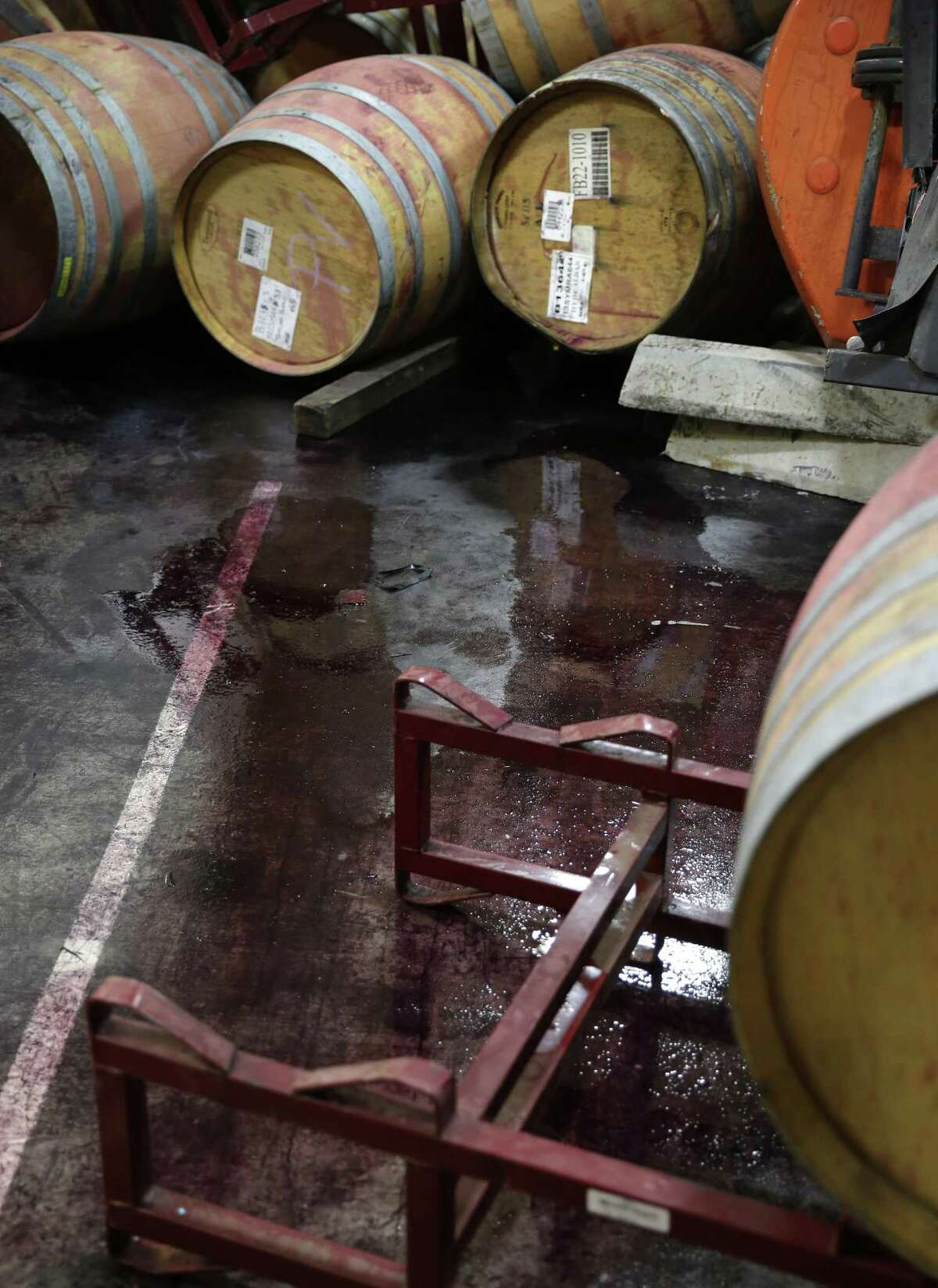 File - This Aug. 25, 2014 file photo shows wine leaking from some of the hundreds of earthquake damaged wine barrels at the Kieu Hoang Winery in Napa, Calif. Napa Valleyís seismically reinforced winery buildings generally held up to the largest earthquake to hit Northern California in a quarter-century, but the precious wine piled inside often did not. (AP Photo/Eric Risberg, file)
