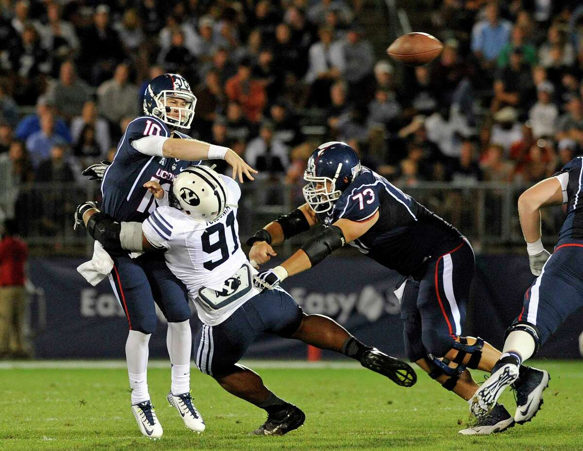 UConn quarterback Chandler Whitmer gets pressured by BYU defensive lineman Travis Tuiloma (91) during the first half of the Huskies' 35-10 loss on Friday night at Rentschler Field in East Hartford.