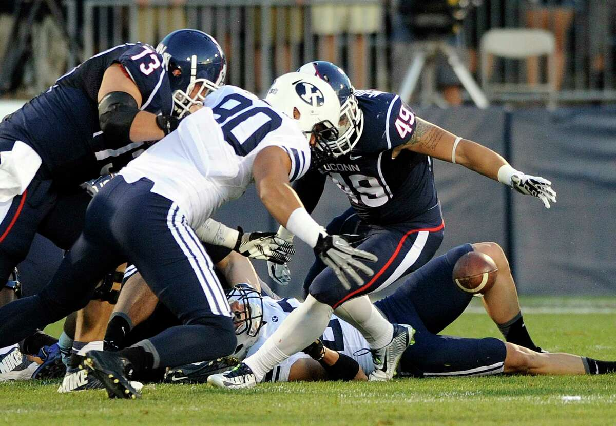 UConn tight end Sean McQuillan (49) and BYU's Bronson Kaufusi (90) fight for a loose ball after a Connecticut fumble during the first half of the Huskies' 35-10 loss on Friday night at Rentschler Field in East Hartford.