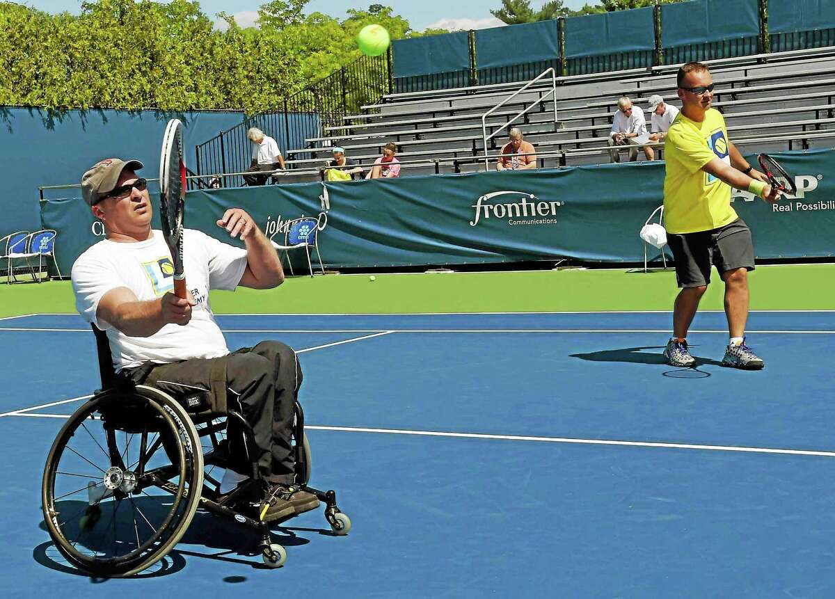 Dr. Ryan Martin of Monroe, left, and Magic Lincer warm up before a doubles match during a wheelchair tennis exhibition on the grandstand court at the Connecticut Open in New Haven on Wednesday.