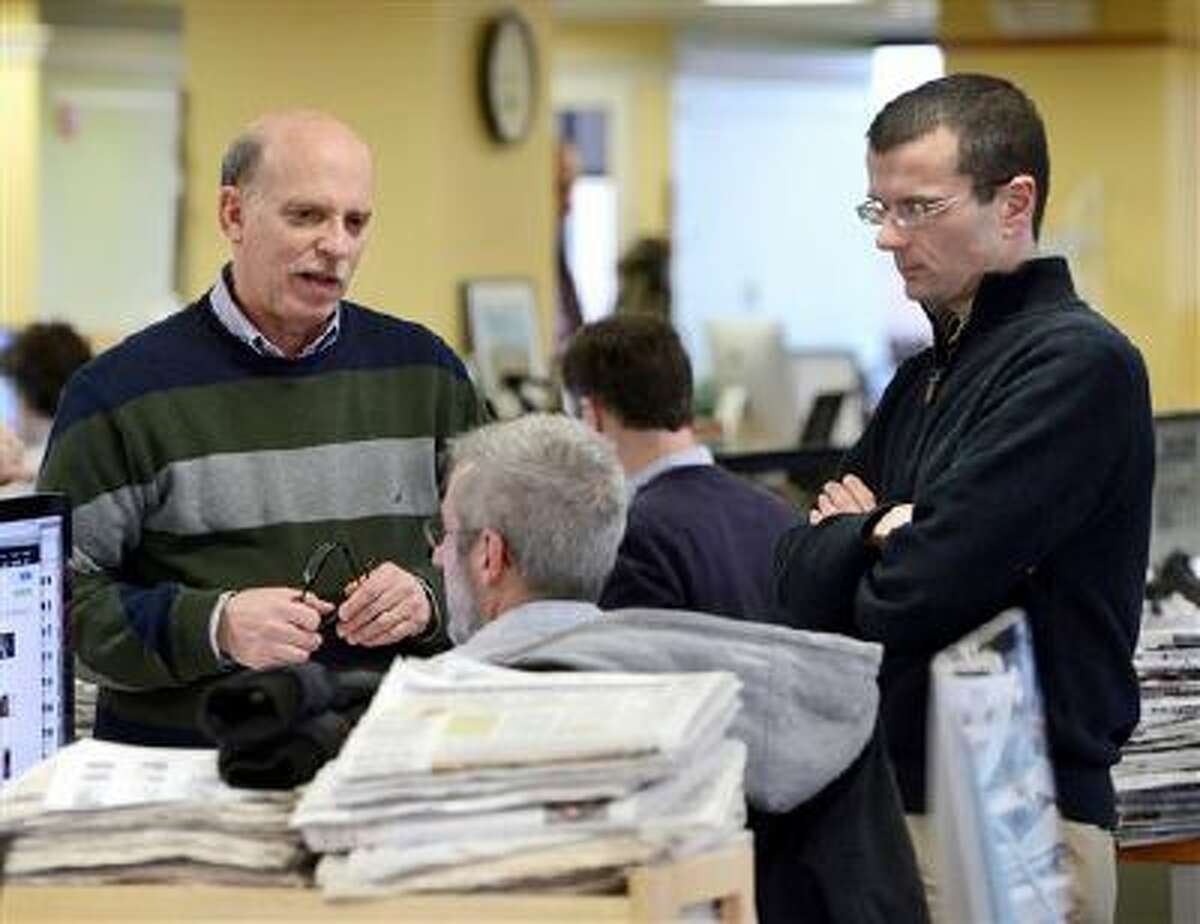 Cliff Schechtman, Portland Press Herald executive editor, left, and Steve Greenlee, managing editor, right, talk with Brian Robitaille, seated, on the copy desk/slot to discuss the next day's front page in Portland, Maine on Tuesday, March 11, 2014. Just three minutes after police officers in the coastal Maine city of Biddeford responded to Derrick Thompson's 911 call and then left the scene, the teenager and his girlfriend were shot dead. But how much were officers told when they were dispatched to Thompson's December 2012 call that he was being threatened? Could they have done more to prevent the killings? Answering questions about their actions took a lawsuit, an appeal and 11 months after state prosecutors turned down the newspaper's request for 911 transcripts. The faceoff was eventually settled in the newspaper's favor by Maine's top court. (AP Photo/Portland Press Herald, John Patriquin)