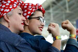Mother and daughter Kim Szerlip and Aubrey Sahouria clench fists like the famous pose while participants attempt a new Rosie the Riveter record at the Home Front Festival and Rosie Rally at the Craneway Pavilion in Richmond, Calif. on Saturday, Aug. 12, 2017. This year's effort to break the Richmond group's previous Guinness world record of 2,229 set last year fell short with an official count of only 1,640 participants costumed as Rosie the Riveter.