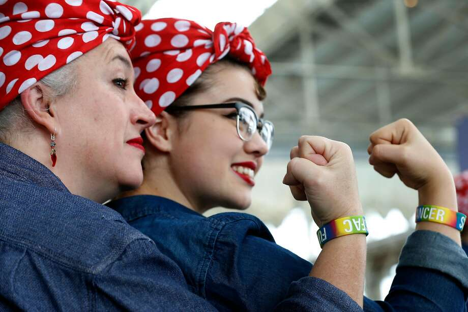 Mother and daughter Kim Szerlip and Aubrey Sahouria clench fists like the famous pose while participants attempt a new Rosie the Riveter record at the Home Front Festival and Rosie Rally at the Craneway Pavilion in Richmond, Calif. on Saturday, Aug. 12, 2017. This year's effort to break the Richmond group's previous Guinness world record of 2,229 set last year fell short with an official count of only 1,640 participants costumed as Rosie the Riveter. Photo: Paul Chinn, The Chronicle