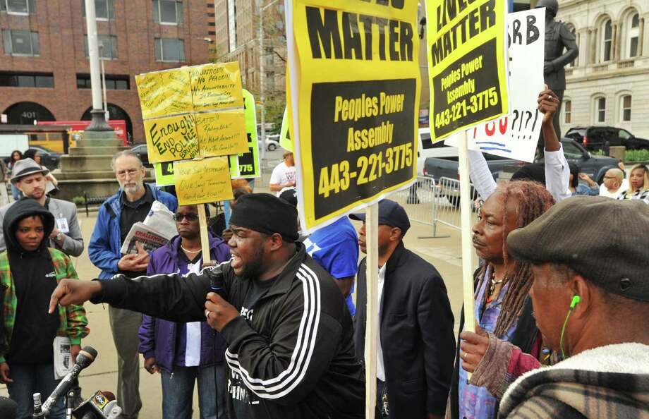 """The Rev. Cortly """"C.D."""" Witherspoon, front left, president of the Baltimore City chapter of the Southern Christian Leadership Conference, speaks at a protest outside City Hall about Freddie Gray in Baltimore, Monday, April 20, 2015. Baltimore's top police officials, mayor and prosecutor sought to calm a """"community on edge"""" Monday while investigating how Gray suffered a fatal spine injury while under arrest. Six officers have been suspended, but investigators say they still don't know how it happened. (Amy Davis/The Baltimore Sun via AP) Photo: AP / The Baltimore Sun"""