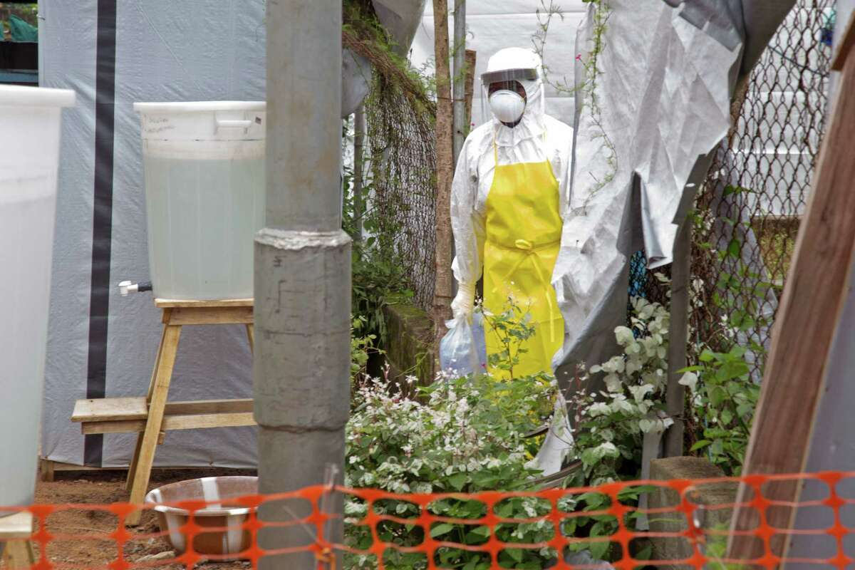 FILE - This Aug. 12, 2014 file photo shows a healthcare worker walking near a Ebola isolation unit wearing protective gear against the virus at Kenema Government Hospital in Kenema, Sierra Leone. Federal researchers next week will start testing humans with an experimental vaccine to prevent the deadly Ebola virus. The National Institutes of Health (NIH) announced Thursday that it is launching the safety trial on a vaccine developed by the agencyís National Institute of Allergy and Infectious Diseases and GlaxoSmithKline. They will test 20 healthy adult volunteers to see if the virus is safe and triggers an adequate response in their immune systems. (AP Photo/ Michael Duff, File)