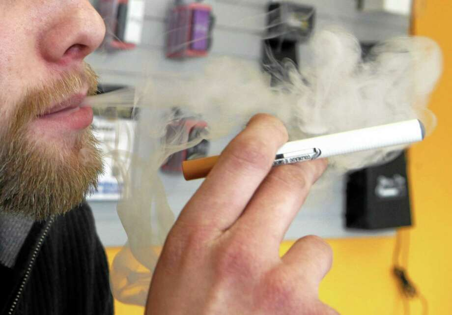 A sales associate demonstrates the use of a electronic cigarette and the smoke like vapor that comes from it in Aurora, Colo., on March 2, 2011. Photo: AP File Photo  / AP