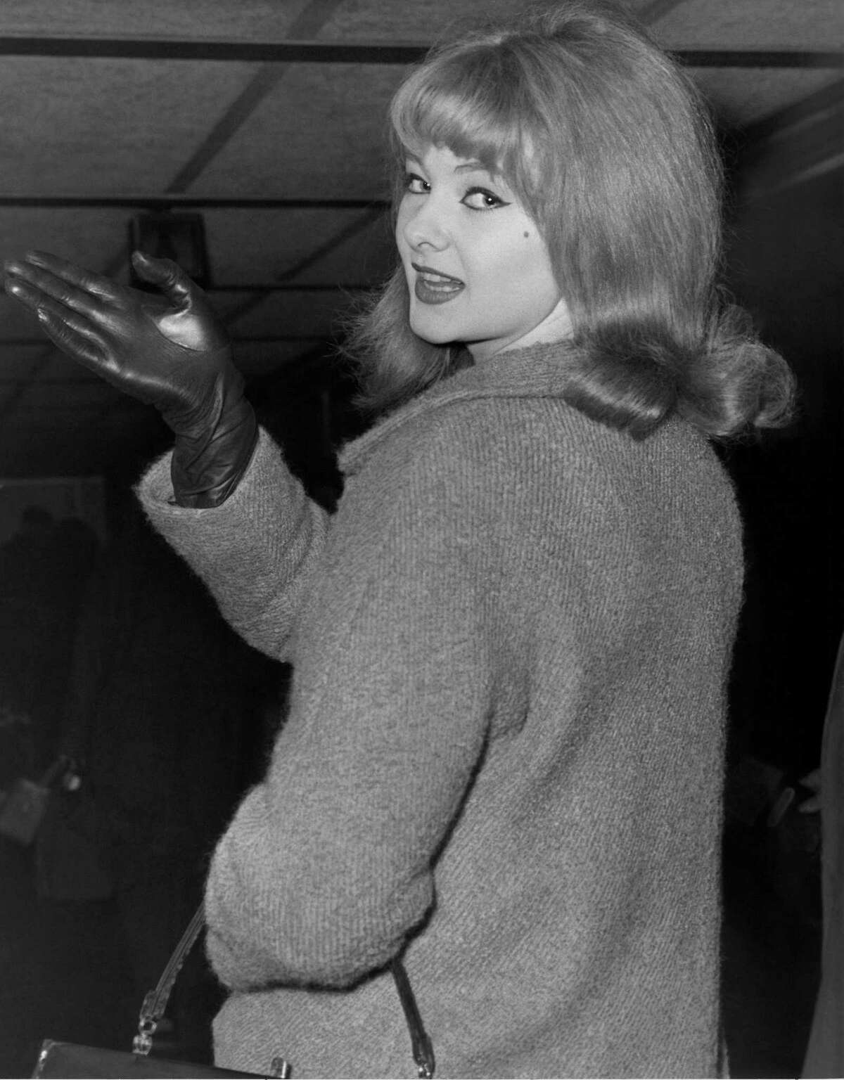 """FILE - In this Jan. 7, 1964 file photo, Mandy Rice-Davies waves goodbye at London Airport as she leaves for Munich for a singing engagement. Mandy Rice-Davies, a key figure in Britain's biggest Cold War political scandal, the ìProfumo Affair,î has died. She was 70. Her PR firm said Friday Dec. 19, 2014, that Rice-Davies died Thursday evening """"after a short battle with cancer."""""""