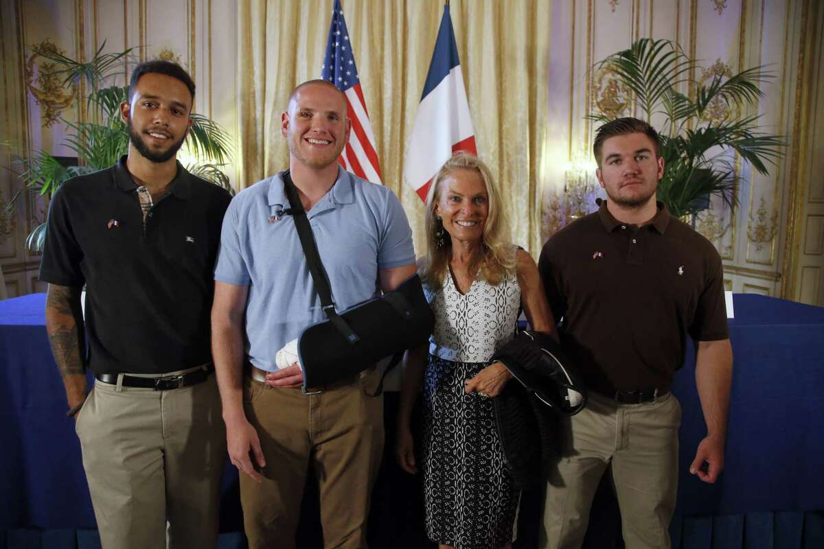Anthony Sadler, a senior at Sacramento University in California, left, U.S. National Guardsman from Roseburg, Oregon, Alek Skarlatos, right, and U.S. Airman Spencer Stone, second from left, pose for photographers with Jane D. Hartley, U.S. Ambassador to France, before a press conference held at the U.S. Ambassador's residence in Paris, France on Aug. 23, 2015. Sadler, Skarlatos and Stone helped foil a potentially deadly attack when they subdued a man armed with an assault rifle and other weapons on board a high-speed train bound for Paris two days ago.