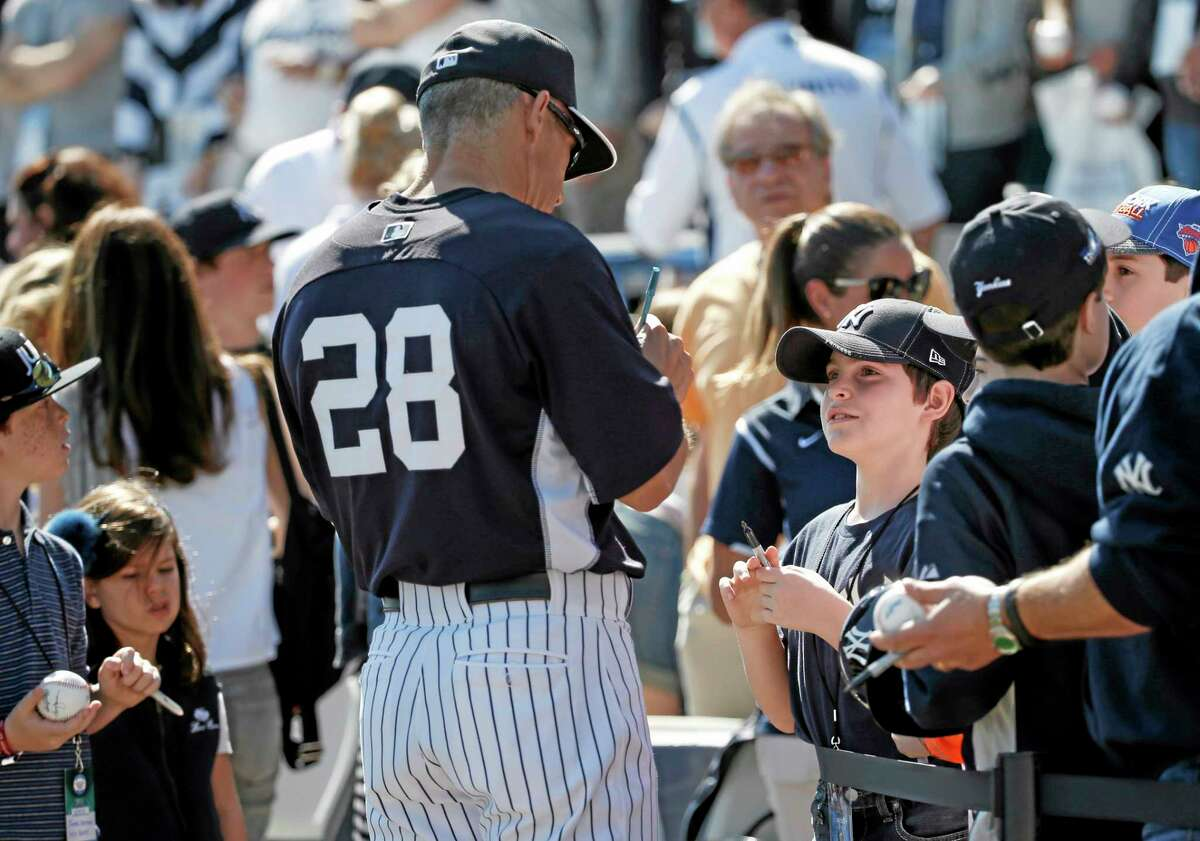 New York Yankees manager Joe Girardi signs autographs for fans who were allowed to watch batting practice from the field before a spring training game against the Boston Red Sox on Tuesday in Tampa, Fla.