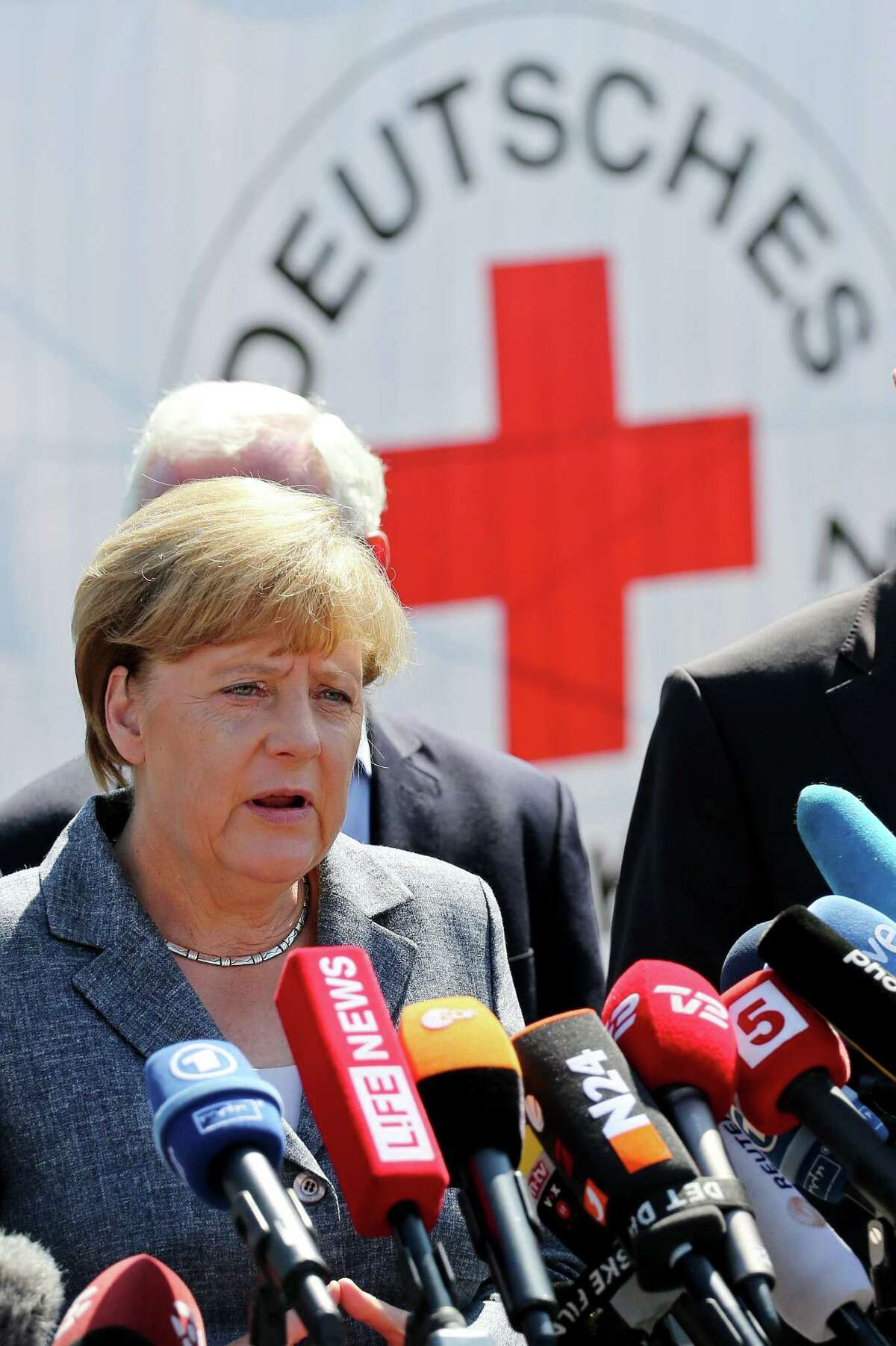 German Chancellor Angela Merkel addresses the media after her visit to a refugee shelter that was attacked by far-right protesters over the weekend in Heidenau,, near Dresden, eastern Germany, Wednesday, Aug. 26, 2015.