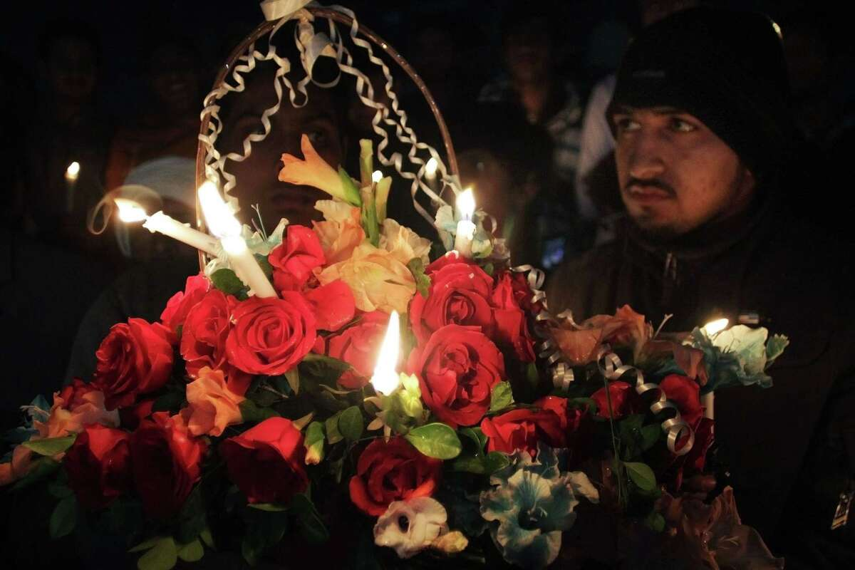 Activists of a religious student group Islami Jamiat Talaba hold a flower basket and candles during vigil for the victims of a school attacked by the Taliban, in Lahore, Pakistan, Dec. 16.