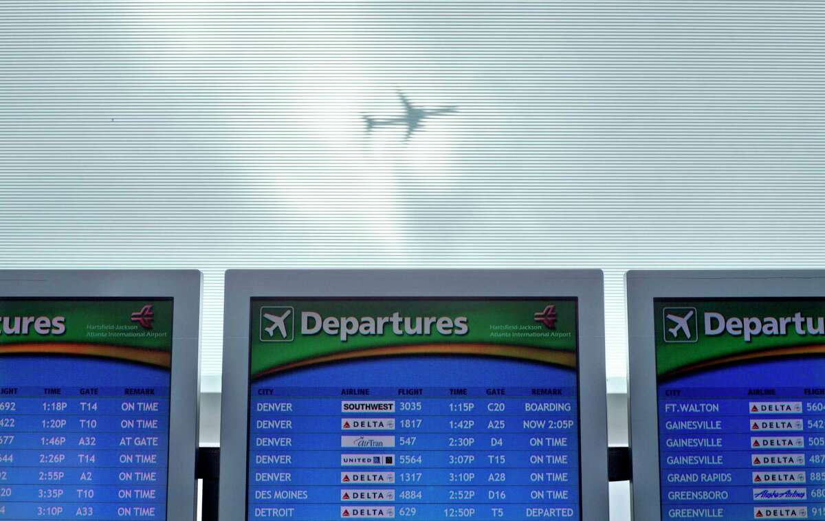 In this Nov. 27, 2013 photo, a plane takes off over a departure board at Hartsfield-Jackson Airport in Atlanta. Caregivers face an assortment of challenges when traveling with a frail relative or friend or with someone with dementia. Packing medications, getting to and from the airport and managing schedules and family activities all can be difficult.