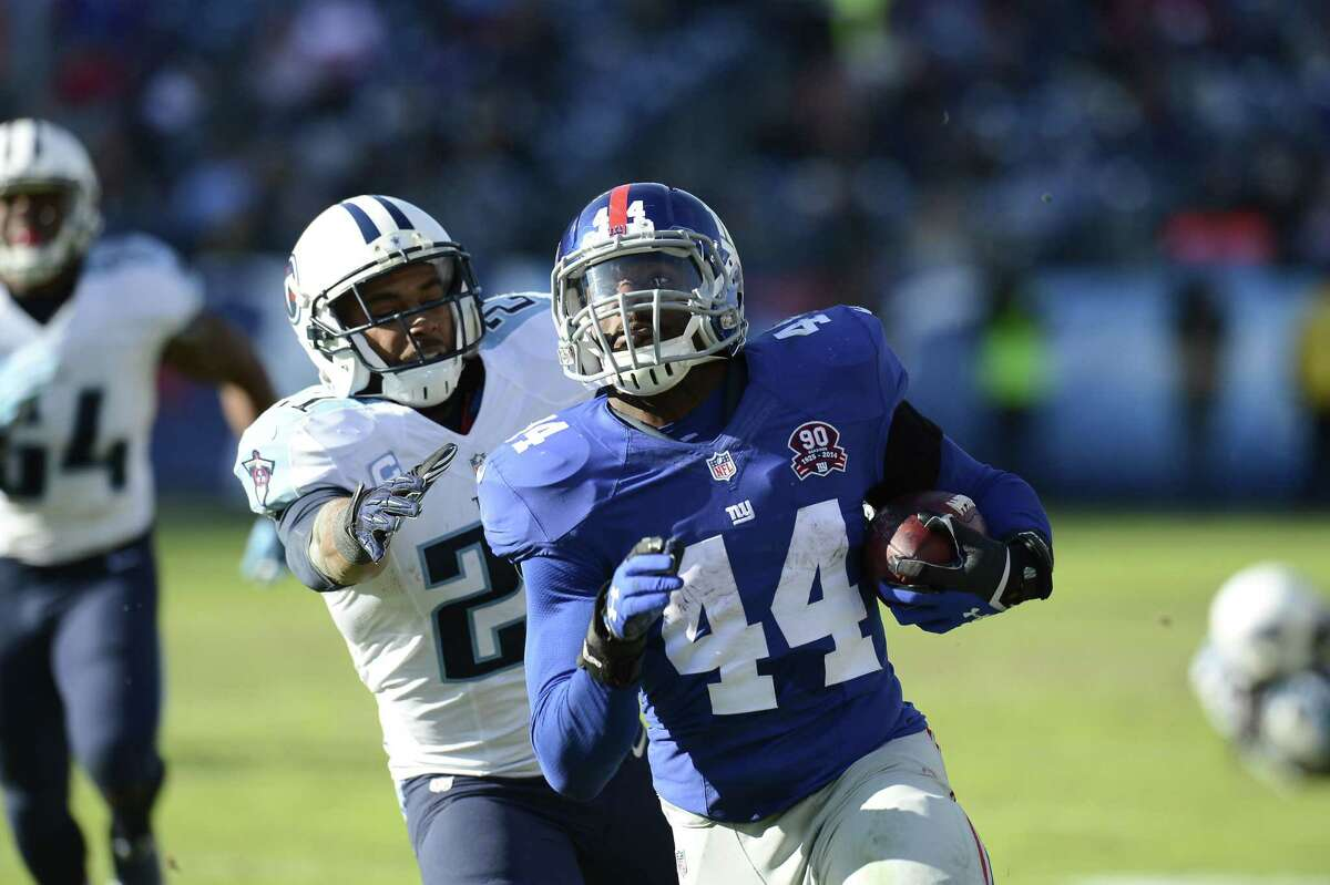 Giants rookie running back Andre Williams (44) scores a touchdown ahead of Titans safety George Wilson during a game earlier this season.