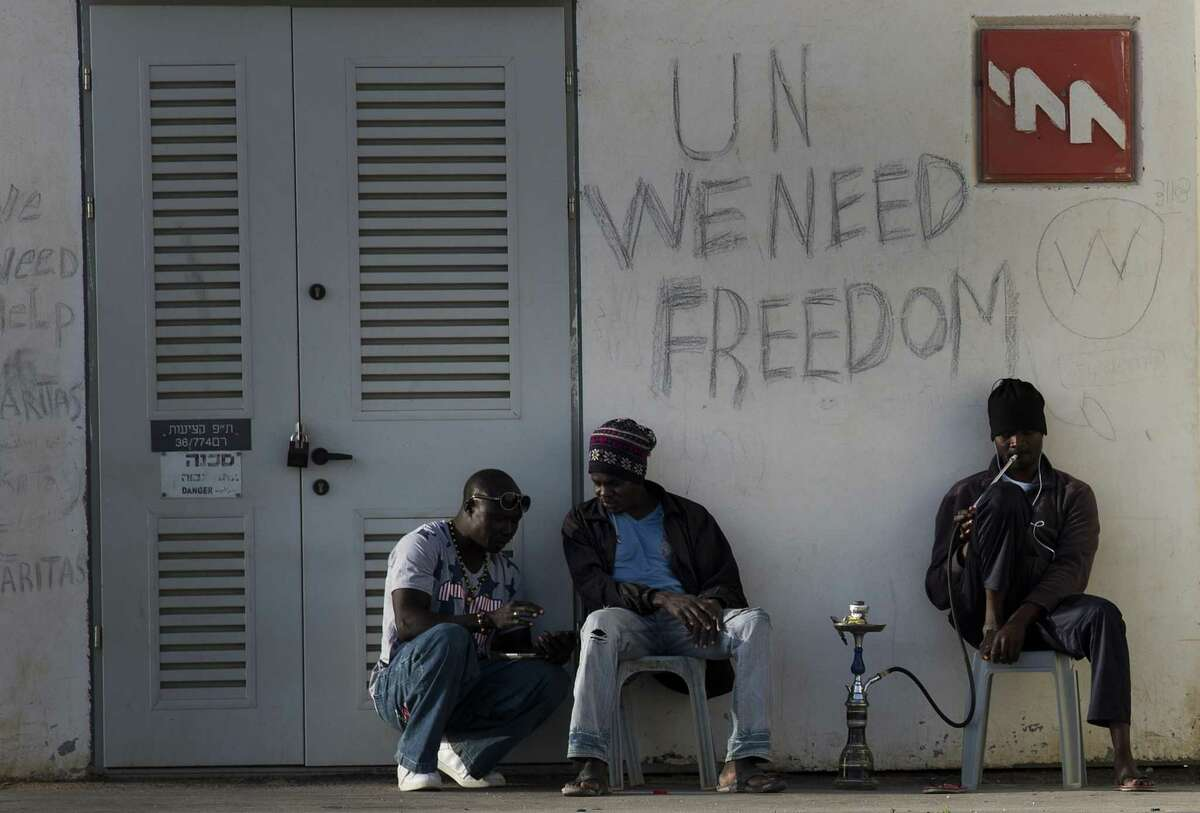 African migrants sit outside Holot detention center in the Negev Desert, southern Israel, Tuesday. Tens of thousands of African migrants have made their way to Israel in recent years. Most of these migrants came from Eritrea, an eastern African nation with one of the worldís most dismal human rights records.