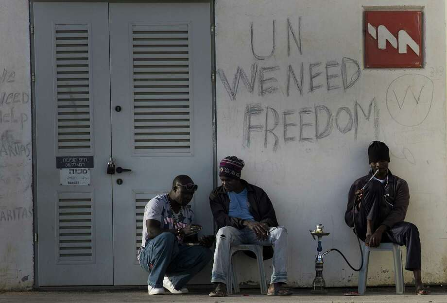 African migrants sit outside Holot detention center in the Negev Desert, southern Israel, Tuesday. Tens of thousands of African migrants have made their way to Israel in recent years. Most of these migrants came from Eritrea, an eastern African nation with one of the worldís most dismal human rights records. Photo: AP Photo  / AP