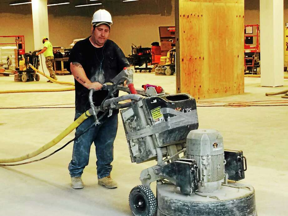 A construction worker pushes a large sander across an unfinished floor at Tanger Outlet Center at Foxwoods Tuesday. Photo: LUTHER TURMELLE — NEW HAVEN REGISTER