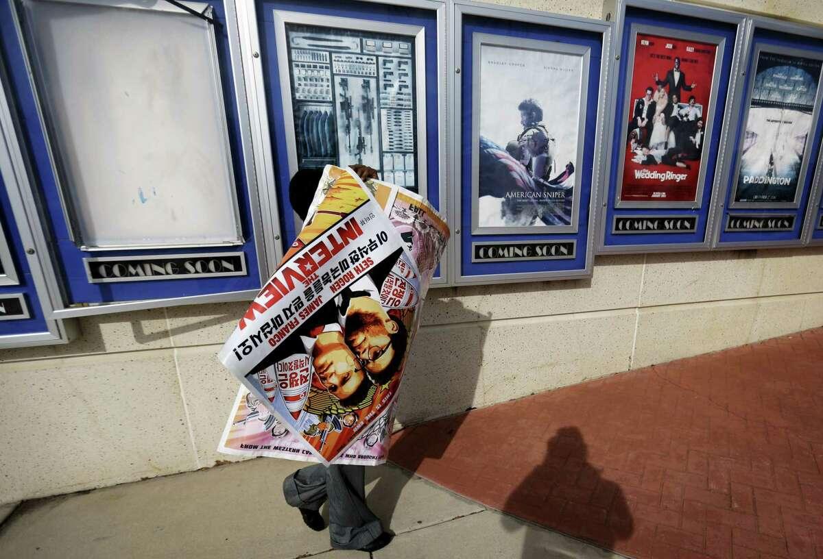 """FILE - In this Dec. 17, 2014 file photo, a poster for the movie """"The Interview"""" is carried away by a worker after being pulled from a display case at a Carmike Cinemas movie theater in Atlanta."""