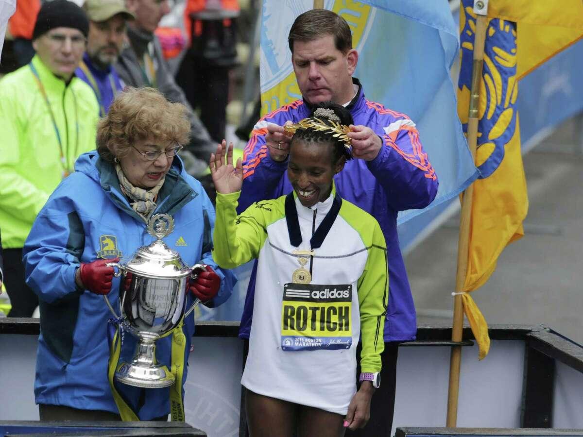 Boston Mayor Marty Walsh crowns Caroline Rotich, of Kenya, after she won the women's division of the Boston Marathon Monday, April 20, 2015 in Boston. (AP Photo/Elise Amendola)