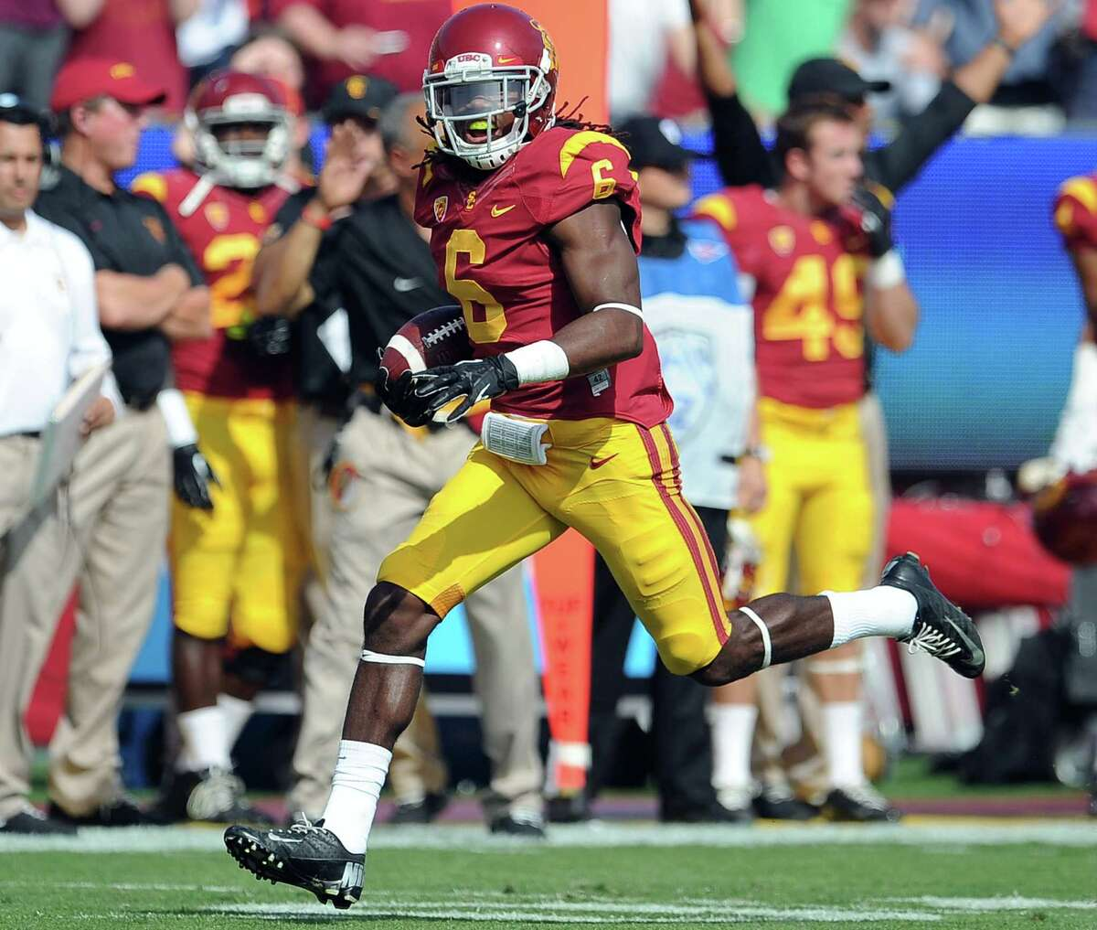 In this Oct. 26, 2013 file photo, Southern California safety Josh Shaw recovers a Utah fumble in a game in Los Angeles.