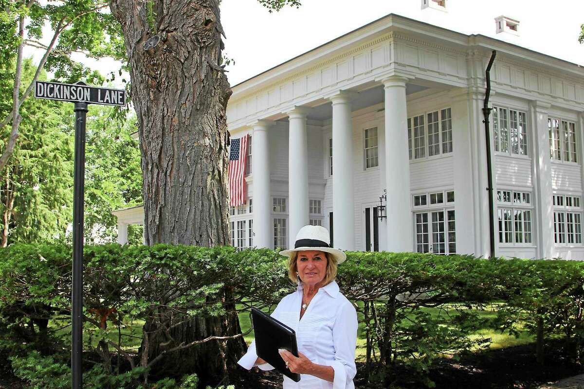 Contributed photo Pat Thompson, Event Chairman for An Afternoon Stroll Through Dickinson History, walks past the former Dickinson family home, one of five private properties that will be opened for public touring on September 13 to benefit the Essex Historical Society.