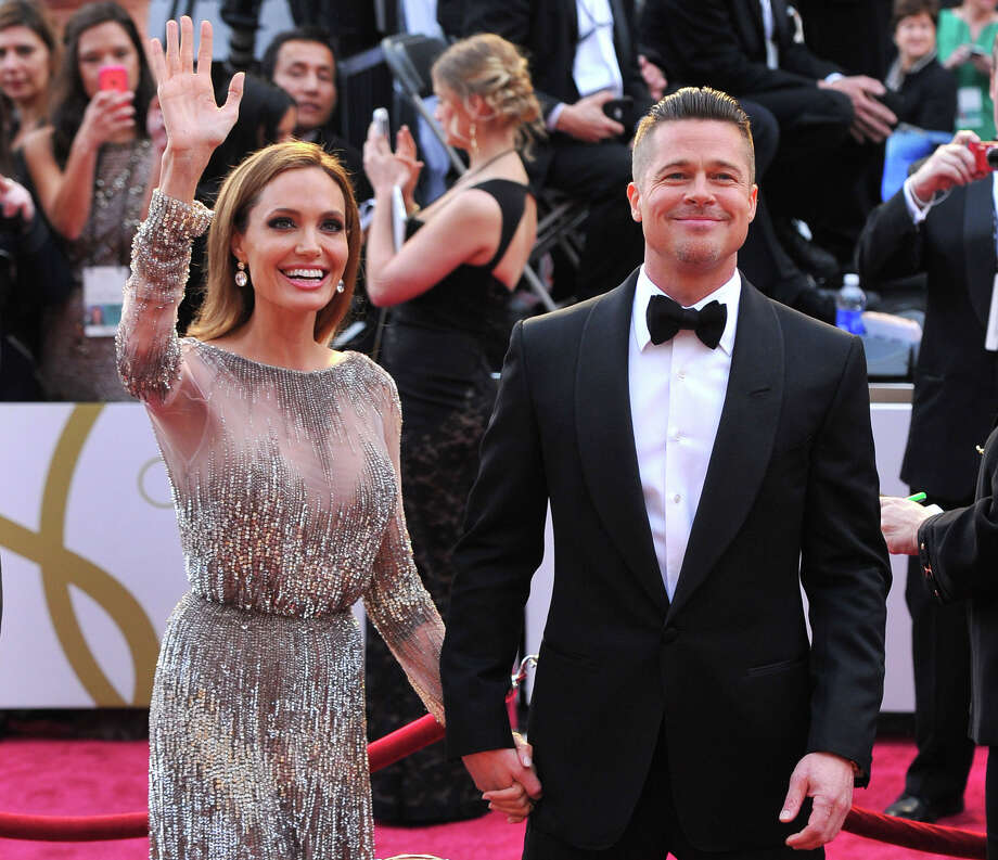 FILE - In this Sunday, March 2, 2014, file photo, Angelina Jolie, left, and Brad Pitt arrive at the Oscars at the Dolby Theatre in Los Angeles. Jolie and Pitt were married Saturday, Aug. 23, 2014, in France, according to a spokesman for the couple. (Photo by Vince Bucci/Invision/AP, File) Photo: Vince Bucci/Invision/AP / Invision