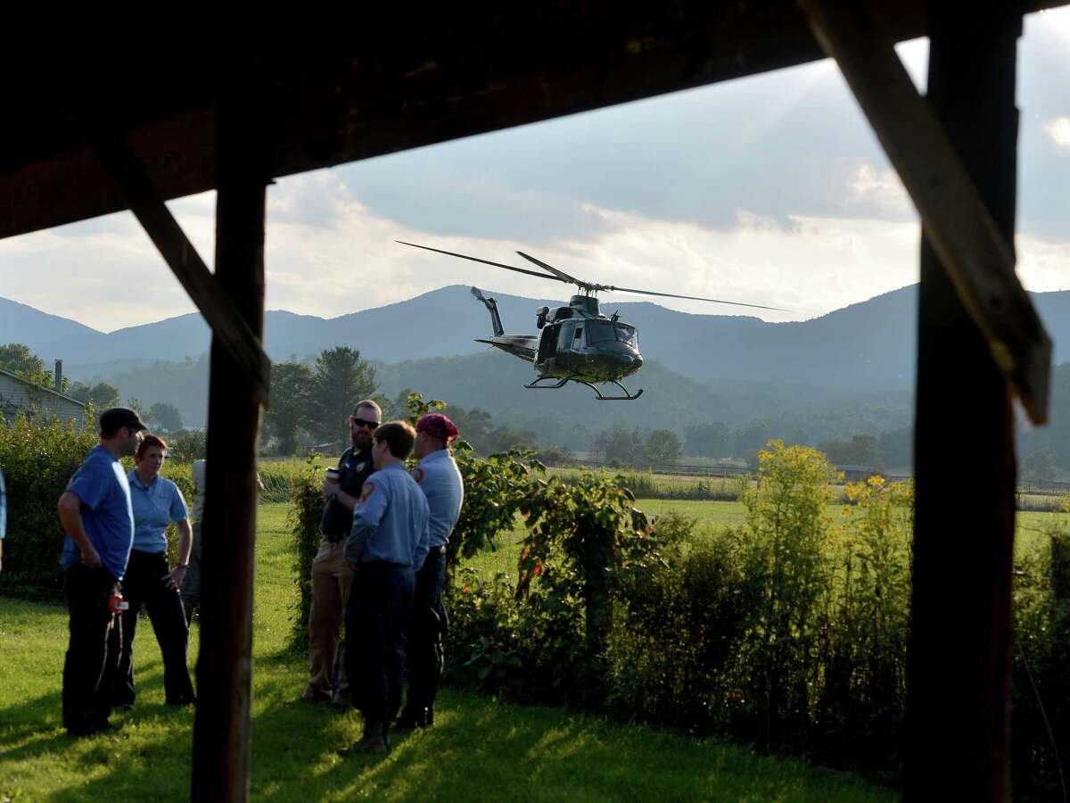 A helicopter takes off near search team members who wait for their turn to join the search for a missing pilot at the mobile command center in Deerfield, Va., on Wednesday, Aug. 27, 2014.