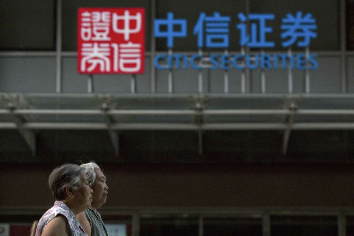 Elderly Chinese women walk near the logo for Citic Securities in Beijing on Aug. 26, 2015. Employees of state-owned Citic Securities Ltd, one of China's biggest securities firms and one current and one former employee of its market regulator are under investigation on suspicion of illegal stock trading, state media reported Wednesday, amid the collapse of a stock price boom.