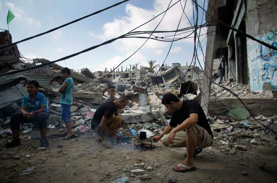 Palestinians make coffee next to their destroyed house in Gaza City's Shijaiyah neighborhood, Wednesday, Aug. 27, 2014.  The third Gaza War in six years appears to have ended in another sort of tie, with both Israel and Hamas claiming the upper hand. Their questionable achievements have come at a big price, especially to long-suffering Palestinians in Gaza.  (AP Photo/Khalil Hamra) Photo: AP / AP