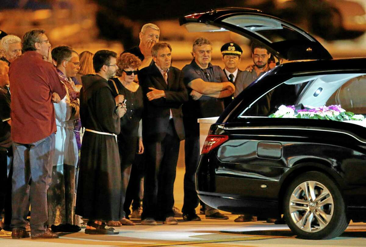 Maria Daniela, fifth right, and Pier Luigi Camilli, fourth right, parents of Associated Press video journalist Simone Camilli, stand in front of the coffin of their son, upon its arrival at Ciampino's military airport, on the outskirts of Rome, Thursday, Aug. 14, 2014. Six people, including an Associated Press video journalist, were killed Wednesday when leftover ordnance believed to have been dropped in an Israeli airstrike blew up in the Gaza Strip. Simone Camilli and his Palestinian translator, Ali Shehda Abu Afash, were covering the aftermath of the war between Israel and Islamic militants in Gaza when they were killed. The blast occurred as Gaza police engineers were trying to defuse unexploded ordnance fired by Israel. (AP Photo/Riccardo De Luca)