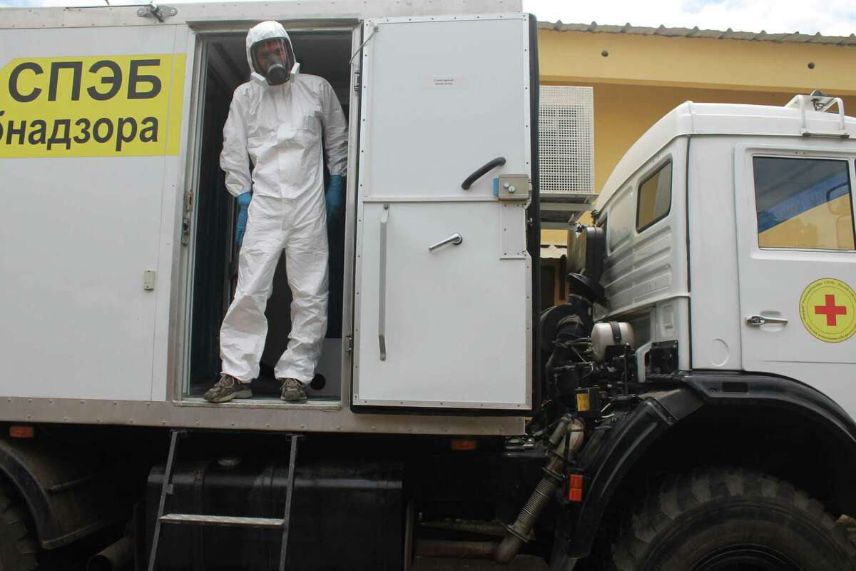 """Russian doctor Valentine Safronov stands Tuesday inside a mobile medical lab donated by the Russian government to assist with the Ebola out-brake in Conakry, Guinea. The Ebola virus may have the """"upper hand"""" in an outbreak that has killed more than 1,400 people in West Africa but experts can stop the virus' spread, a top American health official said at the start of his visit to the hardest-hit countries."""