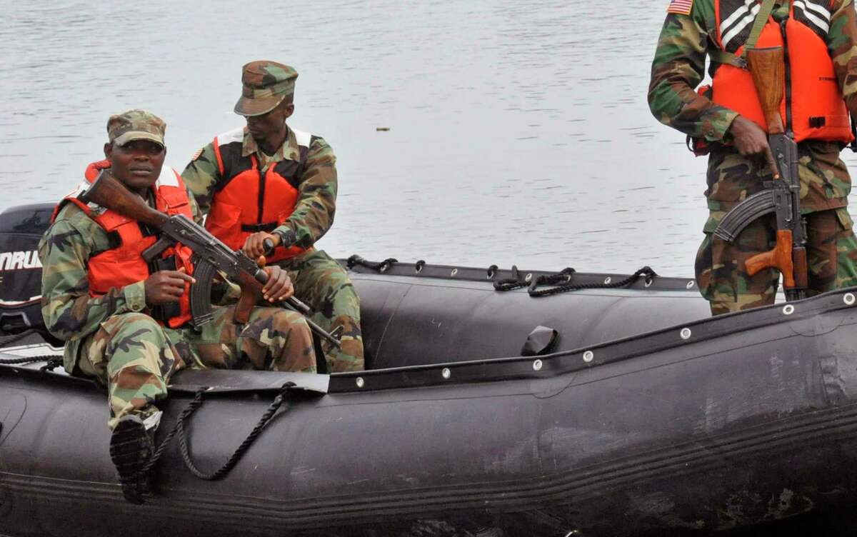 Armed Liberian soldiers patrol the seaside of West Point Wednesday, an area that has been hit hard by the Ebola virus, with local residents not allowed to leave the West Point area, as government forces clamp down on movement to prevent the spread of Ebola, in Monrovia, Liberia.