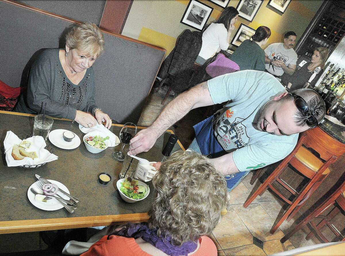 Officer Josh Ward adds fresh grated parmesan cheese to a garden salad for Durham resident Suzanne McNulty as she enjoys lunch with her friend Roberta Pinette, of Middletown at Amici Italian Grill on Main Street in Middletown during last year's Tip-A-Cop fundraiser for Special Olympics.